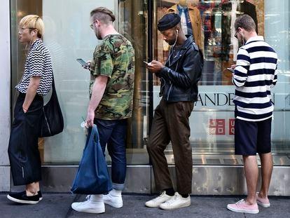 Varias personas usan sus teléfonos móviles mientras hacen cola frente a una tienda en Nueva York.