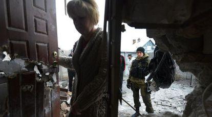 Un miliciano prorruso observa como una mujer entra en su casa tras ser alcanzada por el bombardeo, a las afueras de Donetsk.