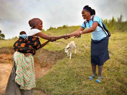 Una trabajadora sanitaria rural saluda a una campesina en la región de El Cabo, en Sudáfrica