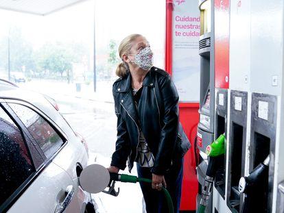 Una mujer reposta combustible en su coche, en Madrid.