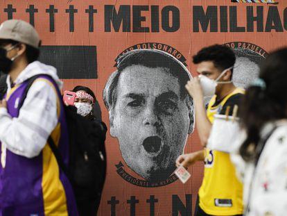 Manifestantes izquierdistas pasan, el sábado pasado en São Paulo, ante un mural que culpa al presidente Bolsonaro del medio millón de muertos por el covid-19.
