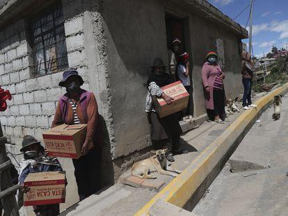 Un grupo de mujeres y niños reciben cajas con ayuda de emergencia para sobrellevar el confinamiento, a las afueras de Quito (Ecuador).