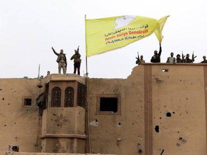 Combatientes de las Fuerzas Democráticas Sirias (FDS) ondean una bandera en Baguz,Siria.