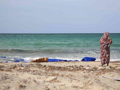 Un mujer permanece junto al mar en un punto de la playa donde quedan restos de barcas de madera y chalecos salvavidas en Sabrata, Libia.