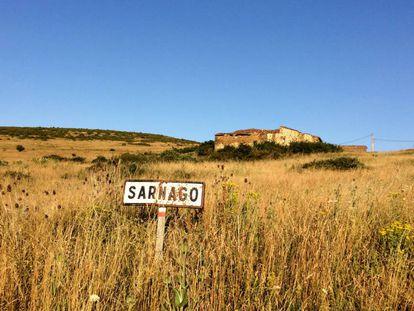 Señal que marcaba el paso por la localidad de Sarnago (Soria), con algunas casas al fondo.
