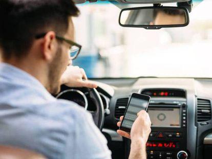 Un joven utiliza su móvil mientras conduce.
