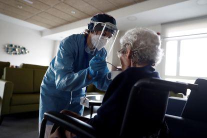 Una cuidadora ayuda a comer a una anciana en la residencia Casablanca, en el barrio madrileño de Villaverde.