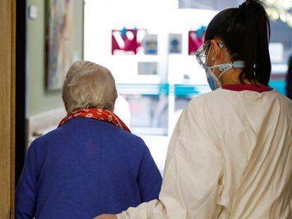 Una trabajadora ayuda a una paciente de la residencia de mayores Vitalia Canillejas, donde se ejercitan terapias para ganar autonomía frente a las secuelas del aislamiento.