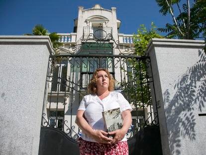 Cristina Keller, presidenta de la asociación Legado de Arturo Soria, posa delante de Villa Menchu con el libro Un paseo por la Ciudad Lineal.