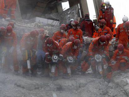 Socorristas turcos intentan rescatar supervivientes entre los cascotes en Ercis.