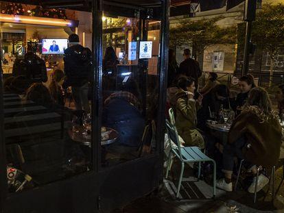 Clientes en un café de París siguen este miércoles el discurso televisado del presidente Macron en el que anuncia un nuevo confinamiento en Francia.