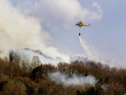 Un helicóptero trata de sofocar el fuego que arrasó ayer bosques del municipio lucense de Samos.