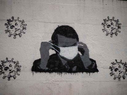 Un grafiti en una calle de Río de Janeiro del presidente Jair Bolsonaro con una mascarilla.