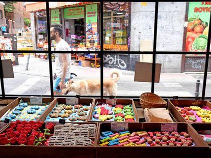 Un chico pasea con un perro delante de una pastelería canina en Madrid.