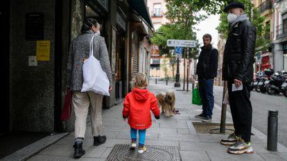 Una mujer camina junto a su hijo este martes por una calle de Madrid, este martes.
