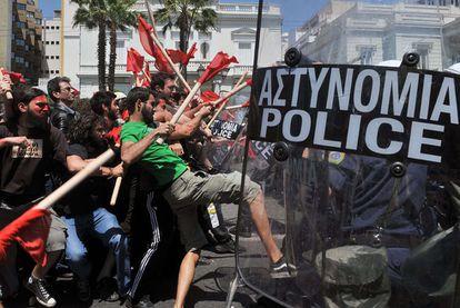 Manifestantes armados con palos y policías chocan en los enfrentamientos registrados ayer en Atenas, durante el Primero de Mayo, ante la sede del Parlamento griego.