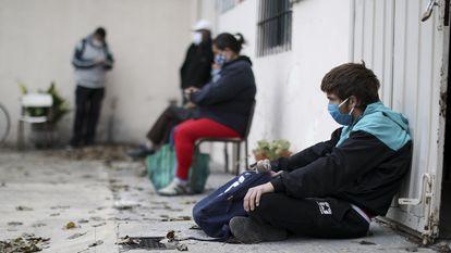 Un grupo de personas, a las puertas de una iglesia de Buenos Aires que funciona como comedor social.