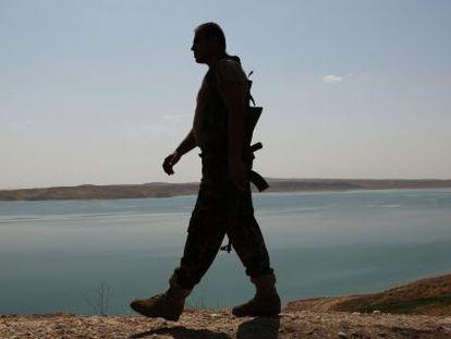 Un soldado kurdo patrulla la presa de Mosul.