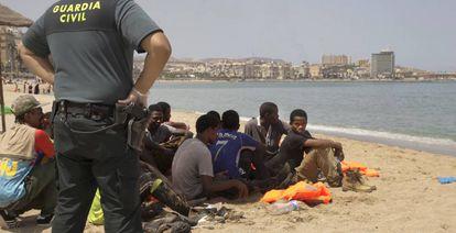 Un grupo de inmigrantes, llegados en patera a una playa de Melilla, el pasado viernes.