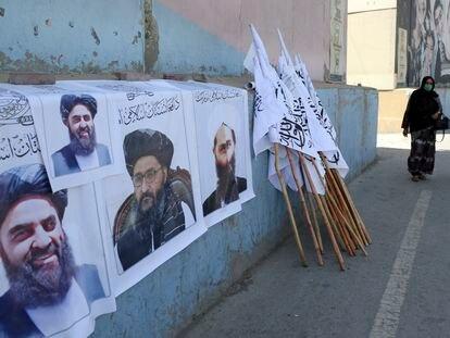 Dos afganas pasan junto un puesto de venta de banderas y carteles con la imagen de líderes talibanes el jueves en Kabul.