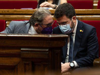 El presidente catalán, Pere Aragonès (der), conversa con el 'conseller' de Economia Jaume Giro (I), durante el pleno de la semana pasada en el Parlament.