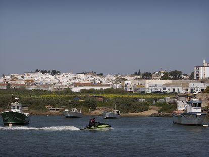 Una moto de agua y unos barcos de pesca navegan en la desembocadura del Guadiana, en Ayamonte, una de las zonas de Huelva en las que crece el tráfico de hachís por la presión en el Estrecho de Gibraltar
