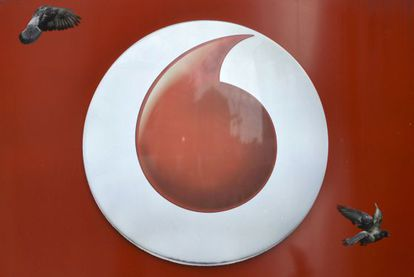 Dos palomas vuelan ante el logotipo de una tienda de Vodafone en Londres.