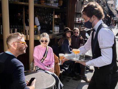 Un camarero atiende a unos clientes en un bar de Londres el pasado 12 de abril.