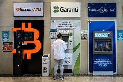 Una mujer usa el cajero de un banco junto a otro de bitcoins en Estambul, la semana pasada.