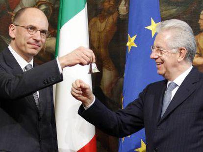 Enrico Letta (izq.), hace sonar una campanilla de plata en señal del inicio de su mandato, junto al jefe del goibierno saliente, Mario Monti.