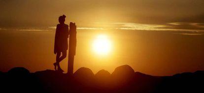 Una mujer disfruta de la llegada del verano con la puesta de sol T