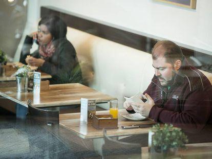 Dos personas desayunan enganchadas a sus dispositivos moviles