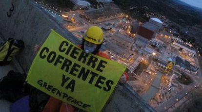 Un activista despliega una pancarta en una de las torres de refrigeración de la central nuclear.