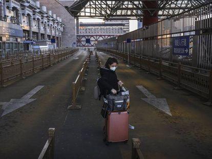 Una mujer en el estacionamiento para taxis vacío de una estación de tren en el oeste de Pekín.