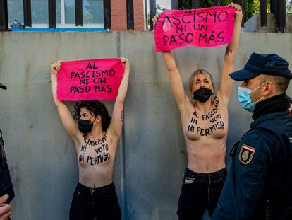 "EDS NOTE: NUDITY - Members of feminist group FEMEN protest with their bare chest reading ""No vote neither permission to fascism"" raise a banner reading ""Not another step to fascism""in front of the poll station where the far right party Vox candidate Rocio Monasterio will vote during the regional election for a new regional assembly in Madrid, Spain, Tuesday, May 4, 2021. Over 5 million Madrid residents are voting Tuesday for a new regional assembly in an election that tests the depths of resistance to lockdown measures and the divide between left and right-wing parties. (AP Photo/Manu Fernandez)"