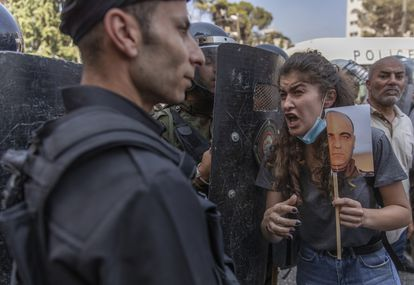 Police block a protesting Palestinian woman with a photo of NIzar Banat in Ramallah on Thursday.