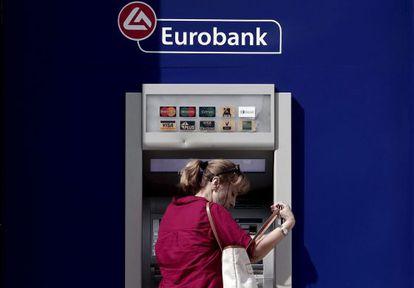 Una mujer saca dinero en un cajero de Eurobank, en Atenas.