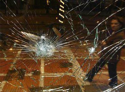 Una mujer pasa delante de unos de los establecimientos atacados en Atenas