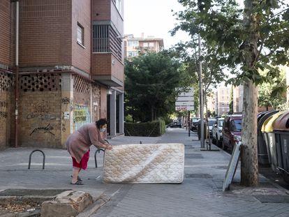 Una mujer arrastra un colchón hasta unos contenedores de basura en el barrio de Pan Bendito, en Carabanchel (Madrid).