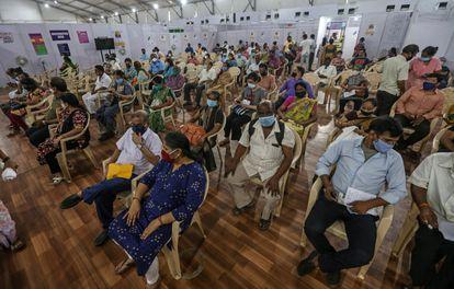 Un grupo de ciudadanos de Bombay espera los efectos de la vacuna contra el coronavirus este viernes en un centro de vacunación.
