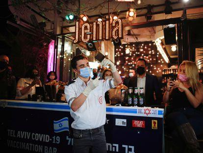 Un sanitario prepara una inyección ante un bar donde se ofrece una bebida gratis a quienes se vacunen contra la covid, el jueves en Tel Aviv.