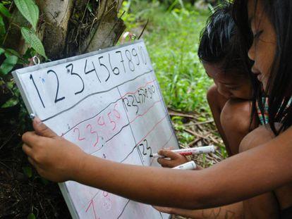 Dos niños Orang Rimba escriben números en una pizarra.