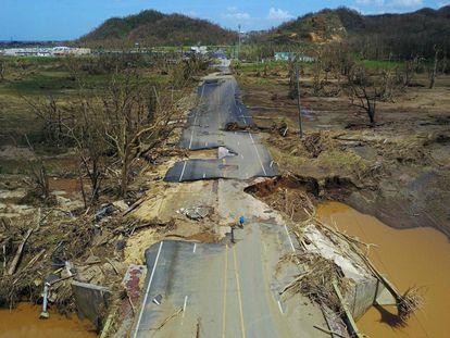 El gobernador de Puerto Rico, Ricardo Rosselló, ha afirmado que el territorio se encuentra en un estado de desastre mayor. En la imagen, una persona en bicicleta intenta avanzar en una carretera destrozada, en Toa Alta (Puerto Rico).