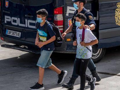 Un policía acompaña a dos menores, el pasado 20 de mayo, en Ceuta.