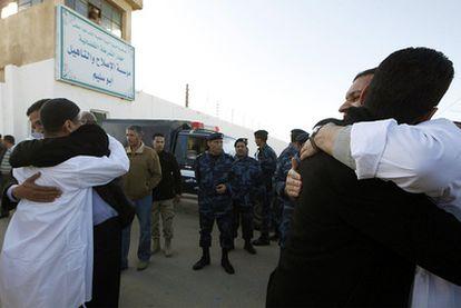 Dos presos del Grupo Islámico Libio (vestidos de blanco) abrazan a familiares tras ser liberados ayer en Trípoli.