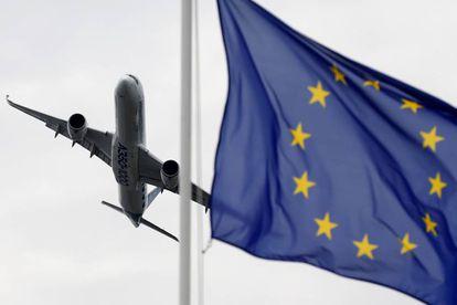 Un  Airbus vuela con una bandera de Europa en primer plano.