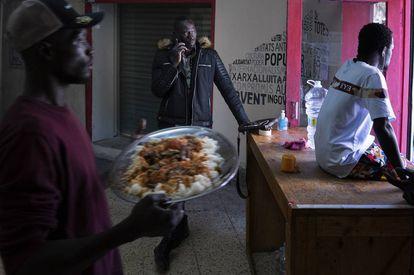 Serigne Mamadou, en el centro de la imagen, en el interior de un local donde preparan comida para los temporeros que duermen en la calle en Lleida.