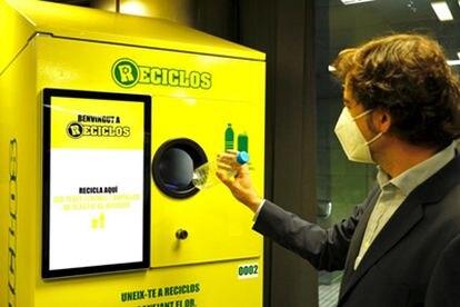 Un usuario deposita una botella de plástico en una de las máquinas de Reciclos en Barcelona.