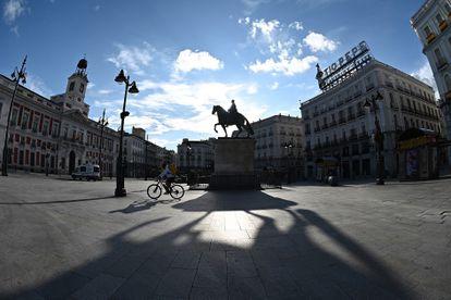 Un repartidor cruza en bicicleta la madrileña Puerta del Sol, vacía, el pasado sábado.