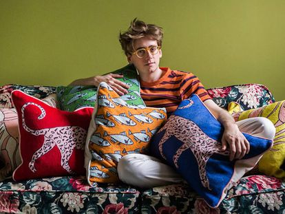 El diseñador Luke Edward Hall entre los cojines que ha diseñado esta primavera para The Rug Company. |